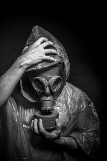 Man in raincoat wearing gas mask against black background