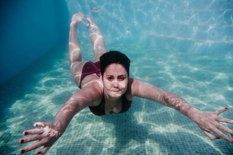 Portrait of woman swimming underwater in pool