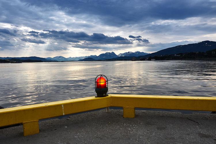 Illuminated lighting equipment at lakeshore against sky