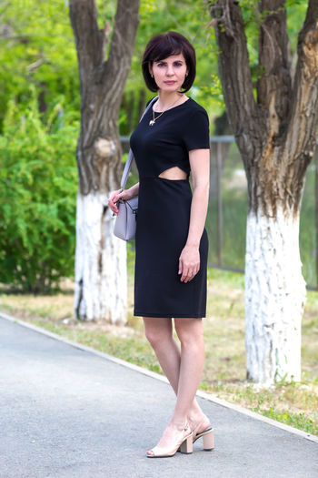 Beautiful slender middle-aged brunette in a black dress on a sunny summer day.