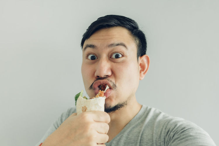 Portrait of man eating ice cream against white background