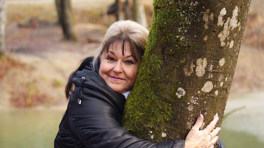 Portrait of senior woman embracing tree trunk