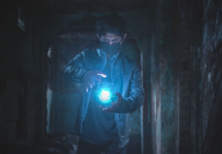 Young man with light painting in abandoned house