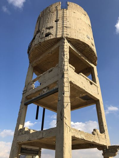 Low angle view of old water tower against sky