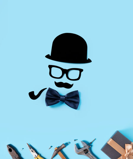 Low angle view of person wearing hat against blue background