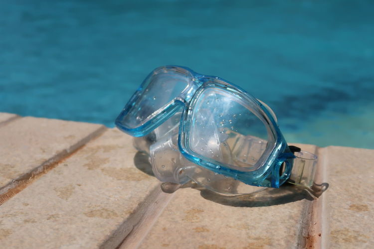Snorkel mask by the pool Goggles Snorkeling Travel Blue Close-up Concept Day Eyewear Lifestyles Mask No People Outdoors Pool Poolside Protection Relax Snorkel Summer Sunlight Swimming Goggles Swimming Pool Transparent Turquoise Colored Vacation Water
