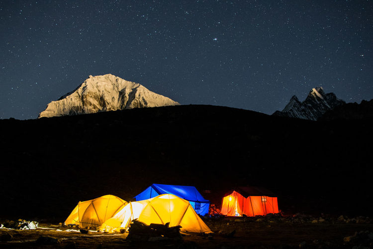 Tent by illuminated buildings against sky at night