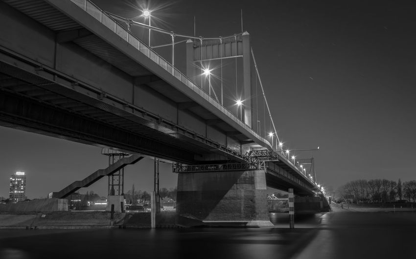 Low angle view of illuminated bridge over river in city against sky at night
