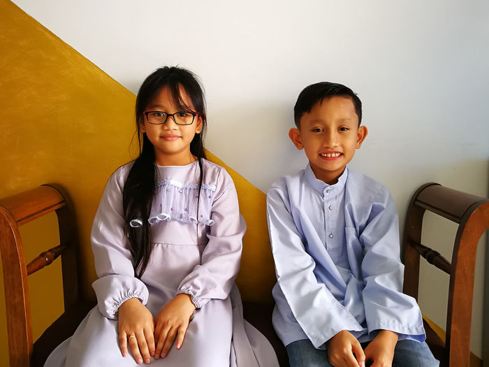 Portrait of smiling siblings sitting on bench at home during eid-ul-fitr