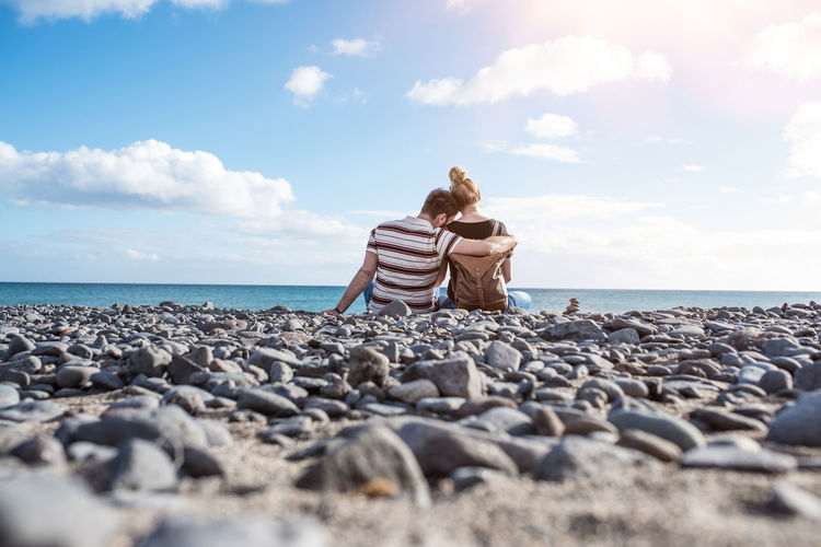 Sunny Beach Bonding Casual Clothing Cloud - Sky Couple - Relationship Day Horizon Over Water Leisure Activity Love Nature Ocean Outdoors Pebble Real People Rear View Rock - Object Scenics Sea Sitting Sky Togetherness Tranquility Two People Water
