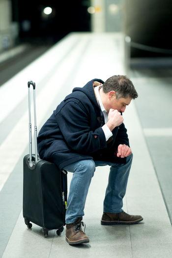 Man checking time while sitting on luggage at railroad station platform