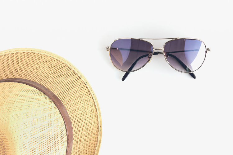 High Angle View Of Sunglasses And Sun Hat Over White Background