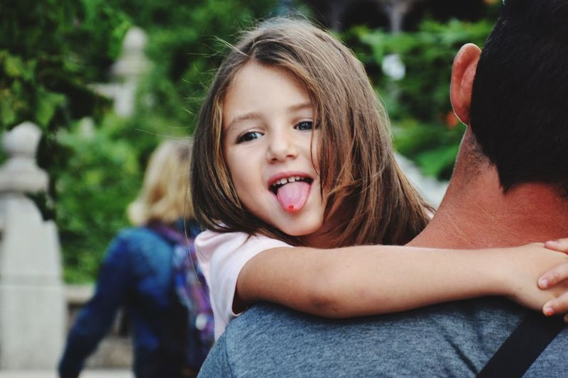 Father carrying playful daughter