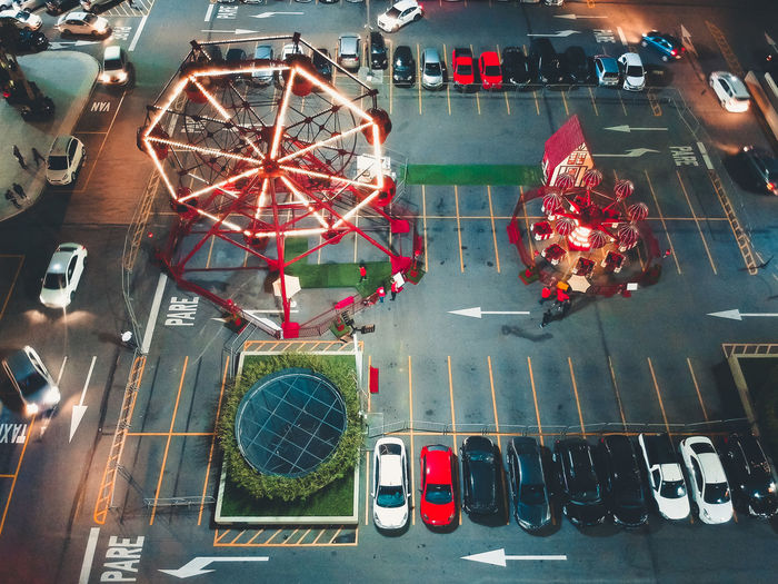 High angle view of ferris wheel on parking lot in city at night