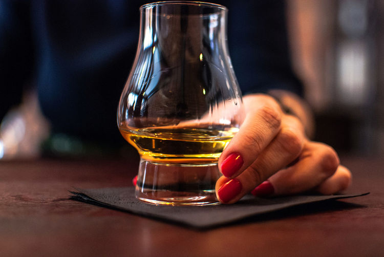 Close-Up Of Woman Holding Whiskey Glass On Table In Bar