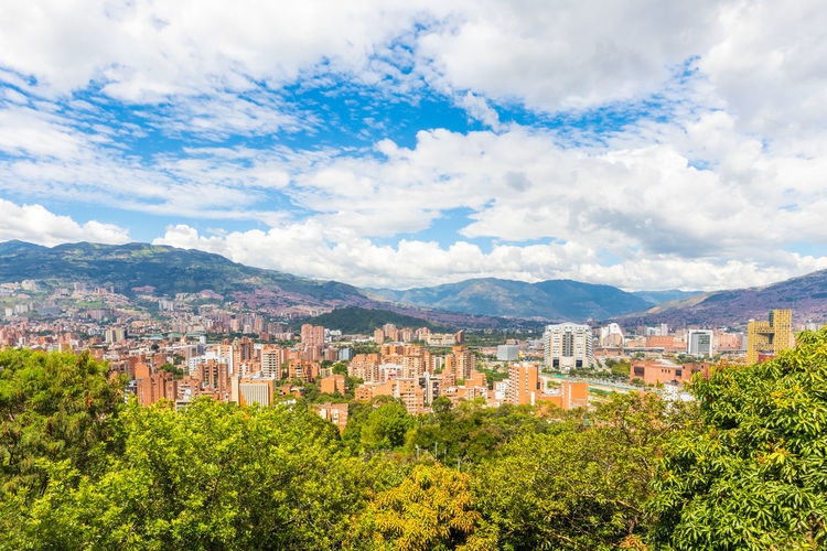 Panoramic view of trees and buildings in city against sky