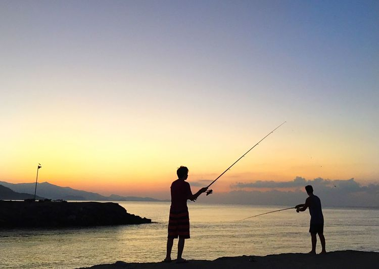 Silhouette of boys fishing on sea during sunset