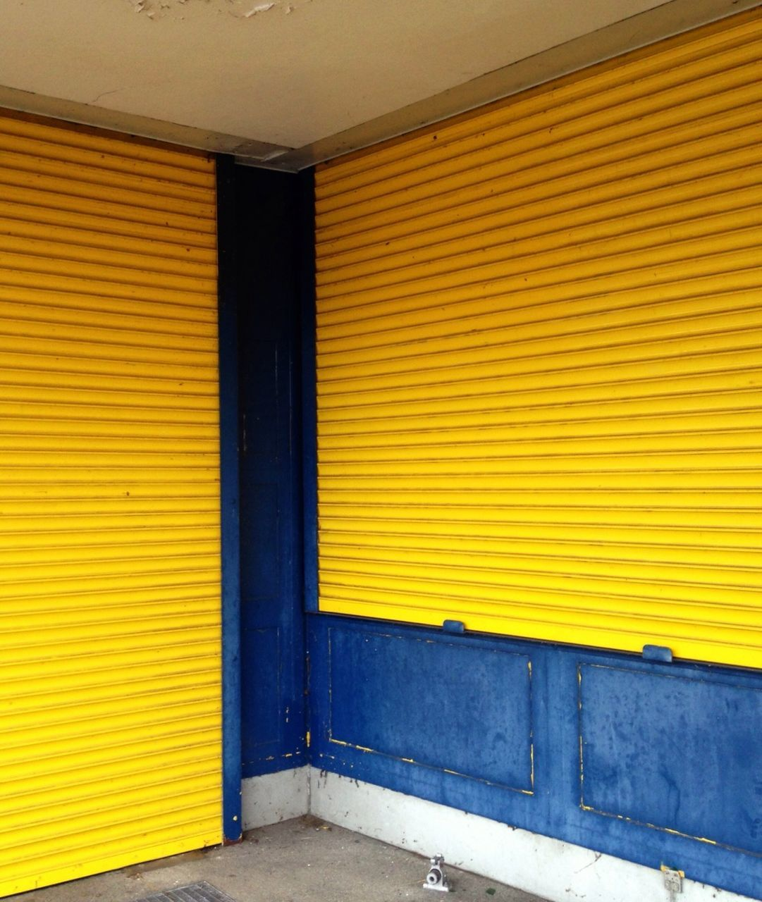 Yellow closed shutters of shop