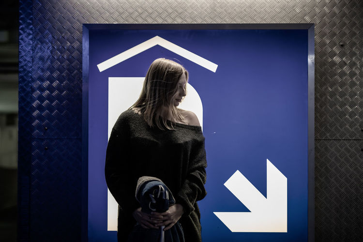 Woman standing against information sign