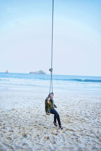 Woman wearing hijab swinging at beach against clear sky