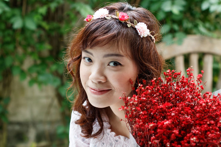 Portrait of happy woman with red flower