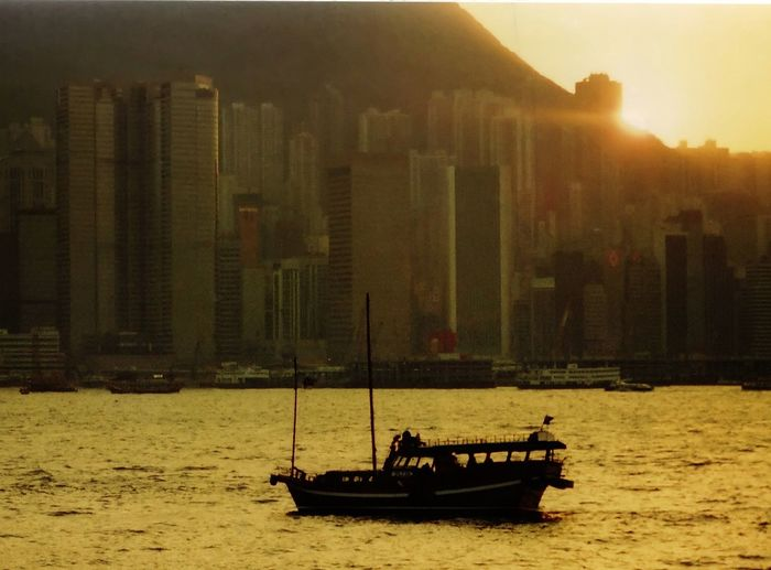 Winter sunset over Victoria Harbour, as seen from Tsimshatsui. HongKong Victoria Harbour Architecture Building Exterior Built Structure City Cityscape Day Kowloon Men Mode Of Transport Nature Nautical Vessel Outdoors People Real People Sailing Sea Skyscraper Transportation Urban Skyline Winter Sunset