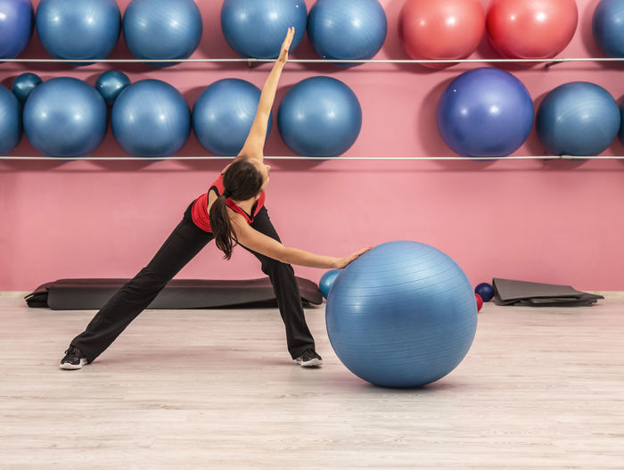 Full length of woman exercising with fitness ball on floor