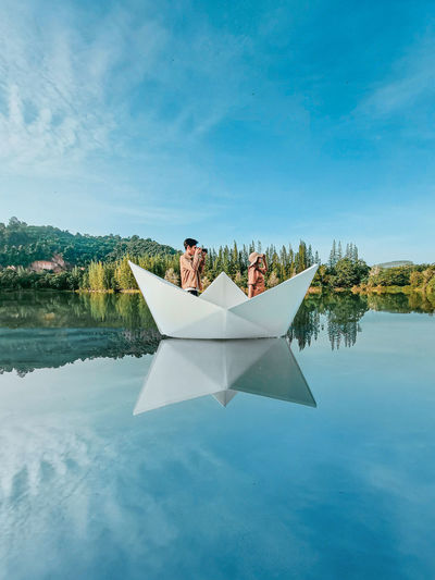 Digital composite image of man sitting by swimming pool against lake