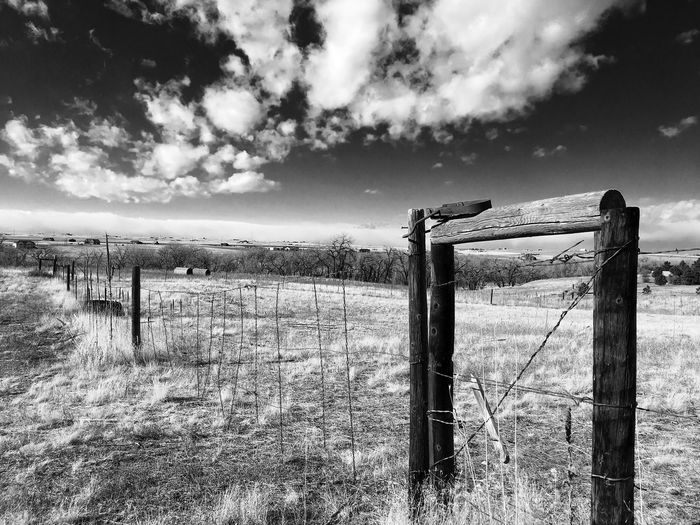 Gates and fences on the range Sky Wood - Material Field Cloud - Sky Outdoors Tree Grass No People Landscape Day Nature Agriculture Fencepost IPhoneography Beauty In Nature EyeEm Best Shots - Black + White Contrast And Lights Fences & Beyond Boundary Wood And Wire Fence Along The Way