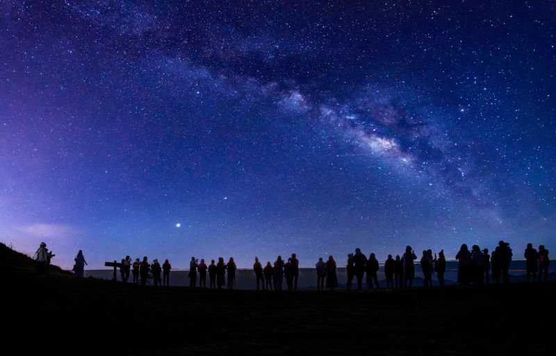 Group of people on field against sky at night