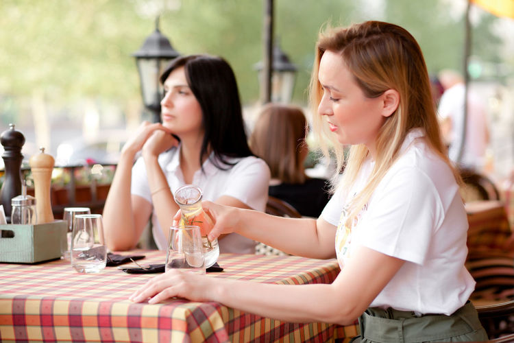Young woman sitting at restaurant table