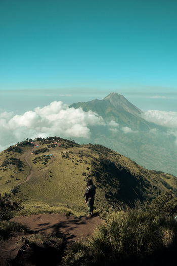 A climber looking merapi volcano from merbabu mountain, indonesia