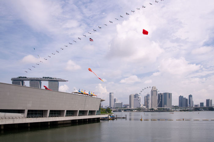 Kites in different colors and shapes over the Marina Bay area, Singapore. Activities Cityscape Colors Kallang Kites Marina Bay Sands Singapore Singapore Flyer Travel Buildings Clouds And Sky Lifestyles Marina Barrage Marina Bay Outdoors River Sky Travel Destinations Visit Water