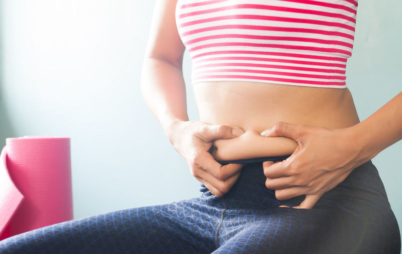 Midsection of woman holding abdomen