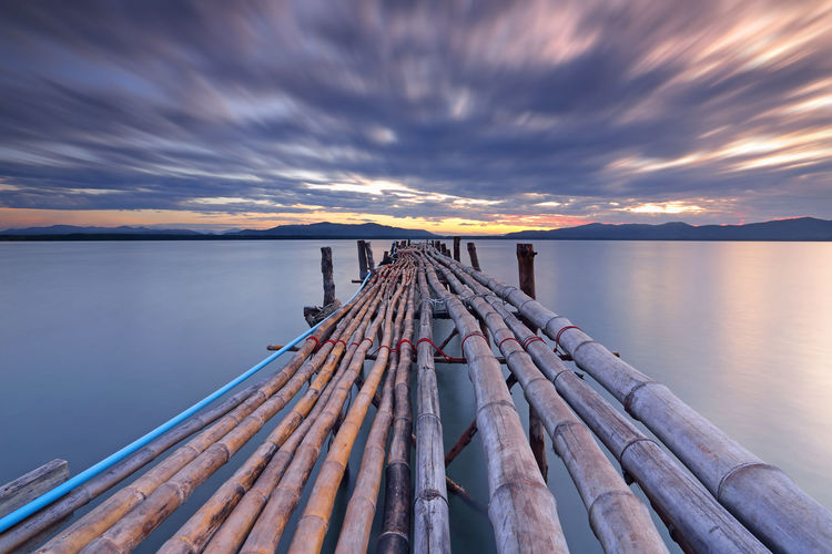 Long Exposure of clouds with long bamboo bridge on the water in the sunrise ASIA Cloudscape Thailland Bamboo - Material Beauty In Nature Cloud - Sky Clouds Moving Dusk Idyllic Lake Landscape Nature No People Outdoors Reflection Scenics - Nature Sky Sunset Tranquil Scene Tranquility Water Waterfront Wood - Material