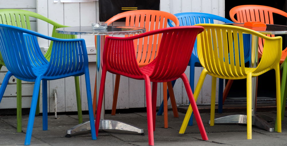 Colorful Empty Chairs With Tables At Sidewalk Cafe