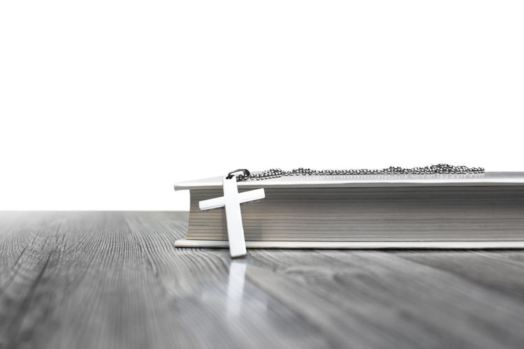 Rosary with bible on table against white background
