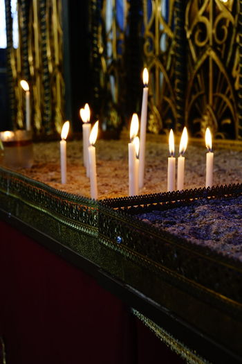 Illuminated candles against building