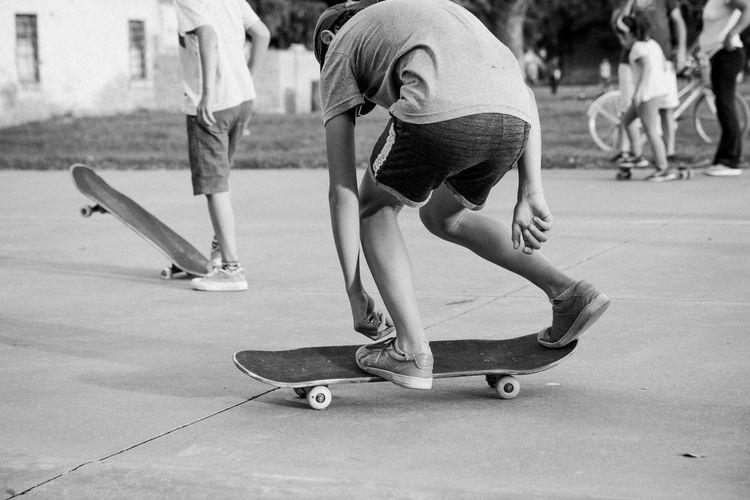 Rear view of people skateboarding in city