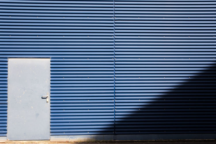 Architectural Detail Architecture Blue Building Exterior Built Structure Close-up Corrugated Corrugated Iron Day Door Garage Industrial Landscapes Light And Shadow Metal No People Outdoors Shutter Sun Light Wall - Building Feature The Graphic City