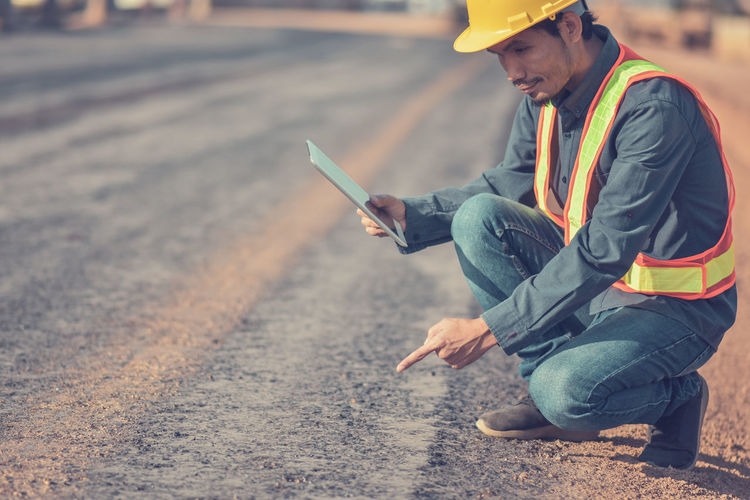 Side view of engineer using digital tablet while crouching on road