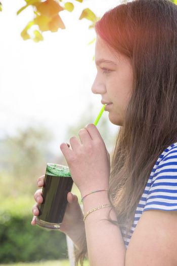 Portrait of woman drinking water