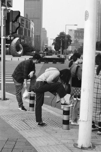 People working on street against buildings in city