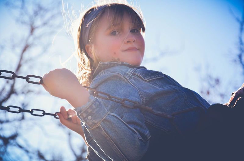 Side view portrait of cute girl swinging at playground during sunny day