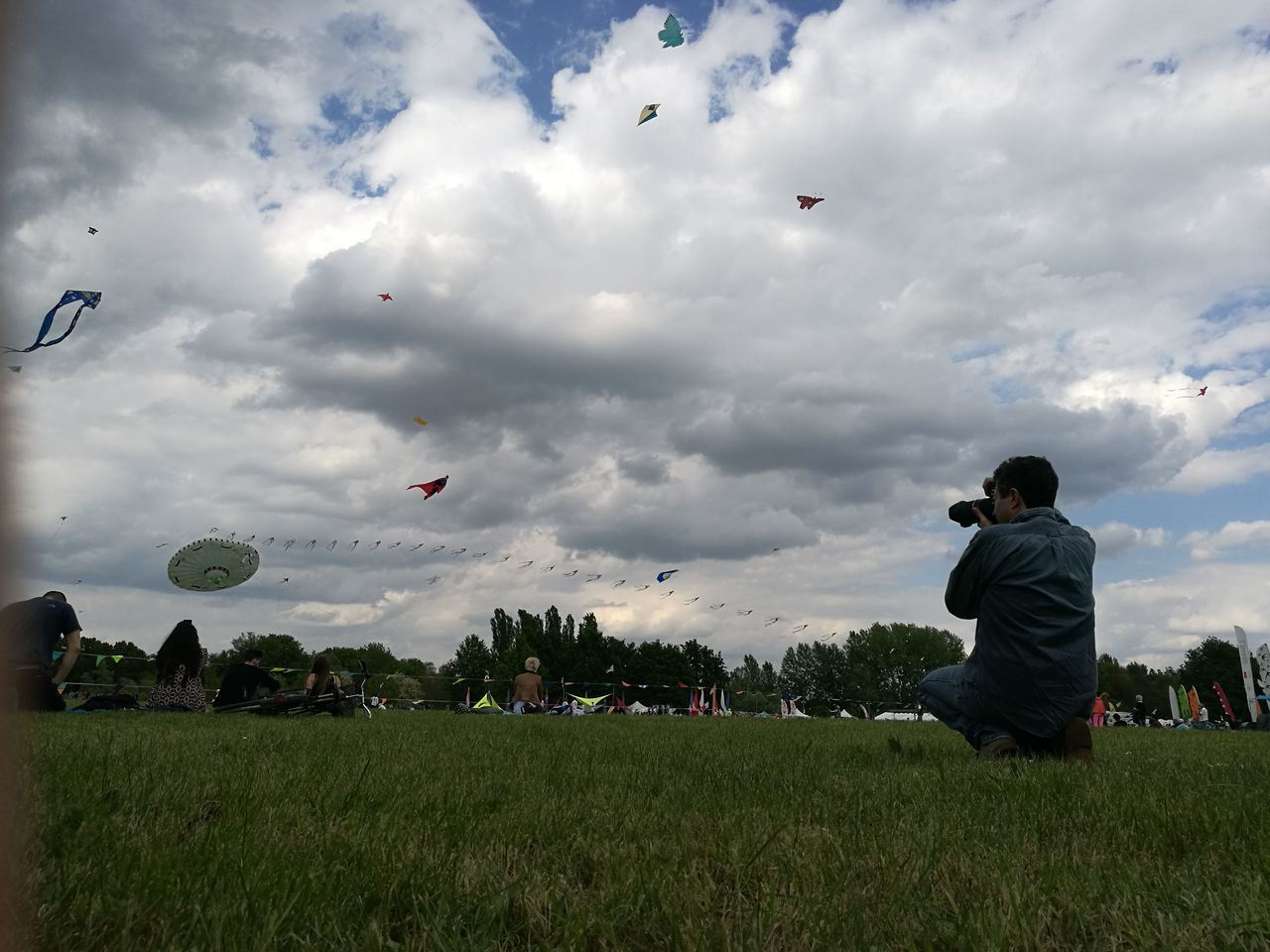 Man Photographing While Crouching On Field Against Sky