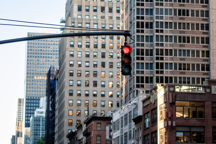 Low angle view of traffic signal against buildings