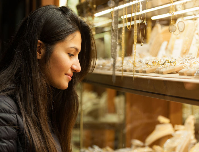 Woman looking at jewelry in store