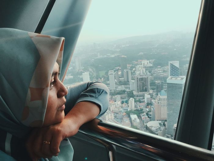 Woman looking at city through window