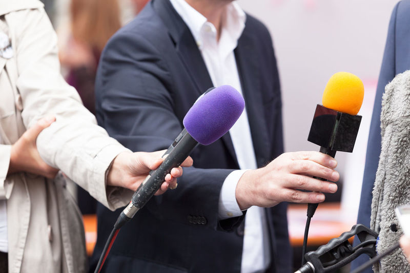 Cropped Hand Of Reporter Holding Microphone