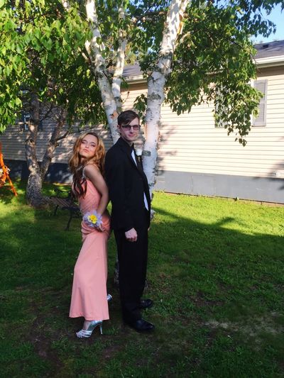 Full Length Of Cheerful Teenage Couple Standing On Grassy Field At Yard During Prom